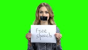 Young woman with taped mouth on green screen. stock video footage