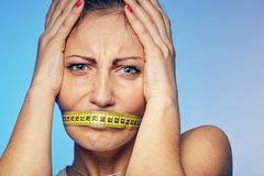 Woman with a taped tape on the lips. She is worried about the diet. A young woman with a taped tape on the lips. She is worried about the diet Stock Image