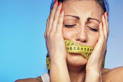 Woman with a taped tape on the lips. She is worried about the diet. A young woman with a taped tape on the lips. She is worried about the diet Royalty Free Stock Photos