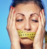 Woman with a taped tape on the lips. She is worried about the diet. A young woman with a taped tape on the lips. She is worried about the diet Stock Photography