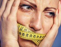 Woman with a taped tape on the lips. She is worried about the diet. A young woman with a taped tape on the lips. She is worried about the diet Stock Images