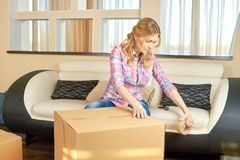 Young woman taping cardboard box. Girl indoors relocation Royalty Free Stock Photos