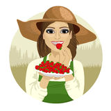 Young woman tasting berry wearing straw hat with plate full of strawberries stock illustration