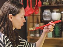 Young woman tasting food in the kitchen stock image