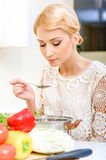 Young woman tasting soup Royalty Free Stock Photography