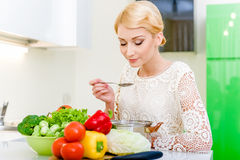 Young woman tasting soup Stock Photos