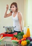 Young woman tasting soup. Young beautiful asian woman tasting soup in kitchen Royalty Free Stock Image