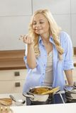 Young woman tasting spaghetti sauce in kitchen Royalty Free Stock Photography