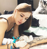 Young woman tattoo artist portrait during creation tattoo on a man hand. Royalty Free Stock Photo