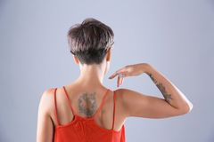Young woman with tattoo. On color background royalty free stock photography