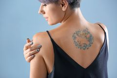 Young woman with tattoo. On color background royalty free stock images