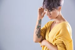Young woman with tattoo on color background. Space for text stock photography