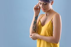 Young woman with tattoo on color background. Space for text royalty free stock photos