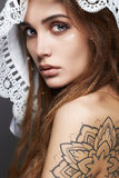 Young woman with tattoo,dreadlocks and lace shawl Royalty Free Stock Image