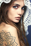 Young woman with tattoo,dreadlocks and lace shawl Royalty Free Stock Photo
