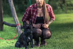 Young woman with tattoo sitting on grass with French Bulldog. In home garden Royalty Free Stock Images