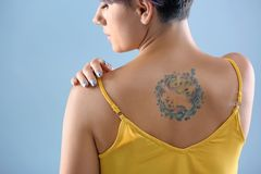 Young woman with tattoo. On color background stock photo