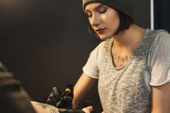 Young woman tattooist doing tattoo on male arm. Concentrated woman tattooist doing tattoo with tattoo machine on male arm. Unusual female profession, copy space Royalty Free Stock Photography