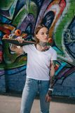 young woman with tattoos holding skateboard over shoulder near wall stock image