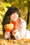 Young  woman with tea cup in the autumn park Stock Photo