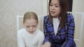 Young woman teacher and little girl sinning and playing the piano together. stock footage