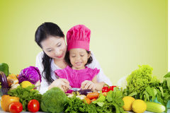 Young woman teaches her daughter to cook Stock Photos