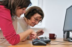Young woman teaches her grandmother. Work with computer - senior lifestyle Royalty Free Stock Photos