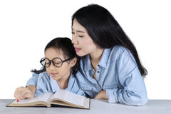 Young woman teaches her kid to read Stock Photo
