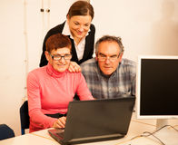Young woman teaching elderly couple of computer skills. Intergenerational transfer of knowledge. Young women teaching elderly couple of computer skills royalty free stock images