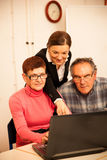 Young woman teaching elderly couple of computer skills. Intergen. Young women teaching elderly couple of computer skills. Intergenerational transfer of knowledge Stock Photography