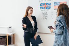 Young woman teaching English to adult students at language school stock photography