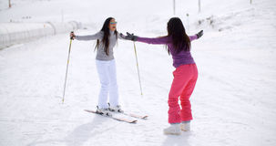 Young woman teaching her friend to ski Stock Photos