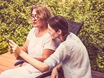 Young woman teaching her mother to use tablet stock images