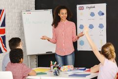 Young woman teaching kids. Young smiling women teaching kids in primary school Royalty Free Stock Image