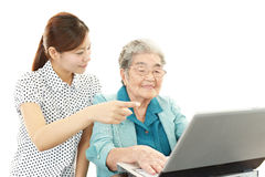 Young woman teaching old woman to use laptop Stock Image
