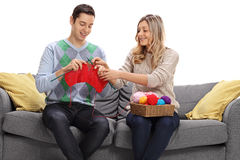 Young woman teaching a young man how to knit Stock Images
