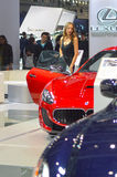 A young woman from the team Maserati near car. Moscow International Automobile Salon Red and Dark Blue Maserati Stock Photos