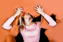Young woman tearing to pieces a brown paper Royalty Free Stock Images