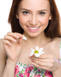 Young woman is tearing up daisy petals Stock Image