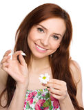 Young woman is tearing up daisy petals Stock Photos