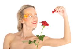 Young woman tears off petals at flower Stock Images