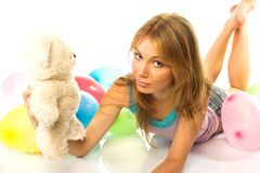 Young woman with teddy. Smiling blond haired woman with teddy bear and party balloons, isolated on white background Stock Photo