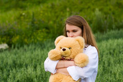 Sad young woman with teddy bear on nature Royalty Free Stock Photos