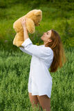 Happy young fashion woman with teddy bear outdoor Royalty Free Stock Photo