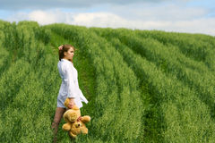 Young fashion woman in white shirt with teddy bear walking outdoor Stock Image