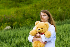 Young fashion woman with teddy bear walking outdoor Royalty Free Stock Image