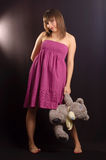 Young woman with teddy bear. Young woman in a pink dress with teddy bear Royalty Free Stock Photo