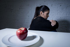 Young woman or teen with apple fruit on dish as symbol of crazy diet in nutrition disorder Stock Photography