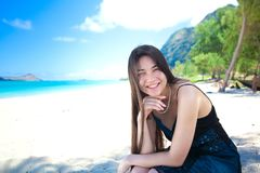 Young woman or teen girl on  Hawaiian beach, smiling. Young woman or teen girl sitting alone on beautiful Hawaiian beach looking happy and smiling, chin on hand Stock Photos