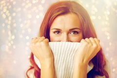 Young woman or teen girl pulling pullover collar. Winter, christmas and people concept - young woman or teen girl pulling up pullover collar Royalty Free Stock Photos